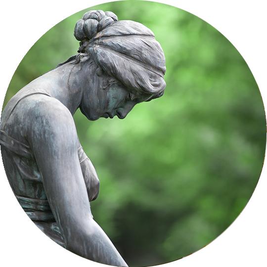 Statue einer trauernden Frau mit gesenktem Kopf