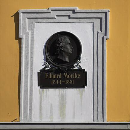 Wandtafel mit einem Bild von Eduard Mörike und der Inschrift 1844-1851 an der Wand eines Gebäudes in Bad Mergentheim.