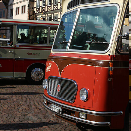 Zwei rote Oldtimerbusse beim Oldtimer Bustreffen auf dem Marktplatz in Bad Mergentheim.
