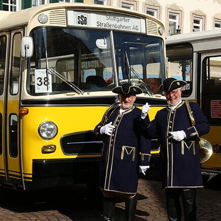 Gelber Oldtimerbus und zwei Personen in traditioneller Kleidung beim Oldtimer Bustreffen auf dem Marktplatz in Bad Mergentheim.