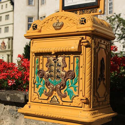 Historischer gelber Briefkasten beim Deutschordensplatz in Bad Mergentheim.