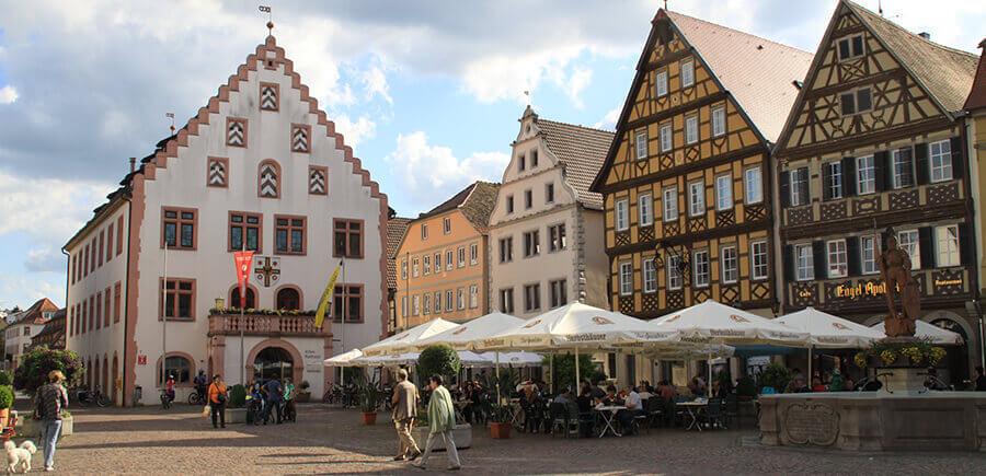 Der belebte Marktplatz Bad Mergentheims mit altem Rathaus, Fachwerkhäusern und Restaurants.