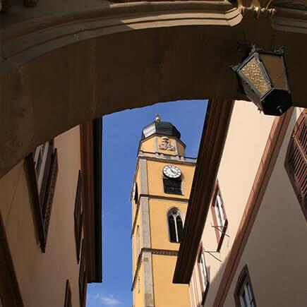 Kirchturm in Bad Mergentheim, aufgenommen aus dem Durchgang zwischen den Zwillingshäusern.