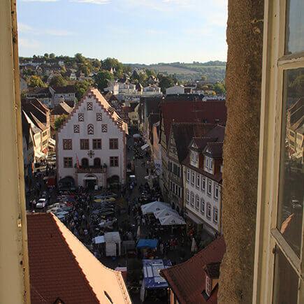 Blick vom Kirchturm auf den Marktplatz in Bad Mergentheim auf dem ein Fest gefeiert wird, im Hintergrund das historische alte Rathaus.
