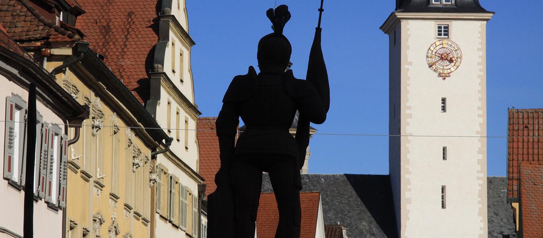 Die Statue des Milchlings im Vordergrund und im Hintergrund der Turm des Deutschordensschloss.