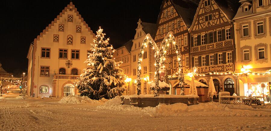 Verschneiter geschmückter Marktplatz mit altem Rathaus und Fachwerkhäusern in Bad Mergentheim.