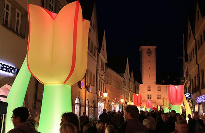 Menschen in der nächtlich illuminierten Burgstraße, der Einkaufsstraße Bad Mergentheims beim Nachtshopping.