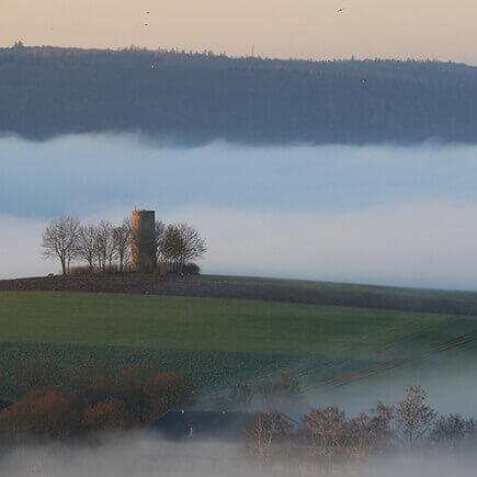 Wachturm in nebliger Landschaft im Lieblichen Taubertal.