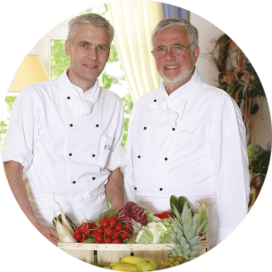 Oliver and Jürgen Schulz, both in a cooking robe with a vegetable box