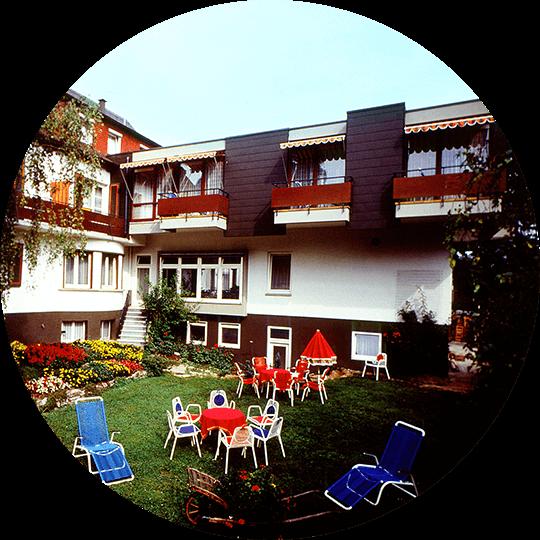 Historisches Bild des Gartens mit Liegestühlen auf der Wiese des Hotel Alexa um 1982