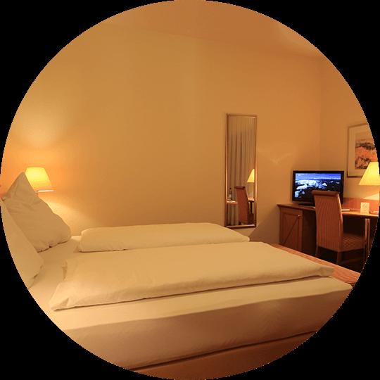 Doppelbett in einem Standard-Doppelzimmer mit TV im Hotel Alexa Bad Mergentheim