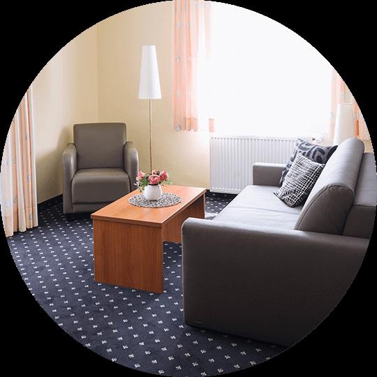 Wohnbereich der Suite Otto mit Sofa und Sessel im Hotel Alexa Bad Mergentheim